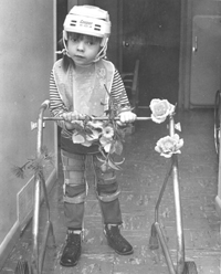 A young Glenda wearing long legged braces, standing with her walker.