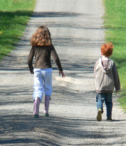 Girl and boy walking along a road, at some distance apart