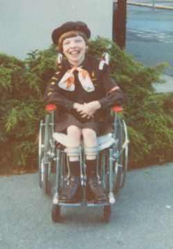 A young Glenda sitting in her red wheelchair, wearing her Brownie uniform with a smile across her face