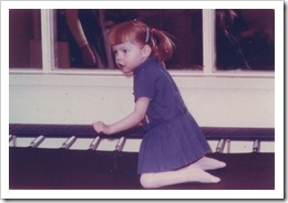 A young Glenda bouncing on a trampoline