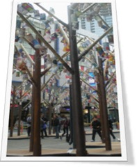 Paper lanterns by Taiwanese children hanging from metal tree forms in public art display