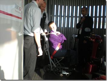 Glenda on aisle chair being wheeled on board the plane