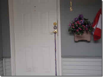 Purple door pull hanging on white front door