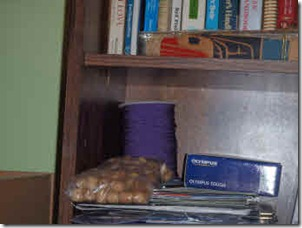 Spool of purple cord and beads on bookshelf