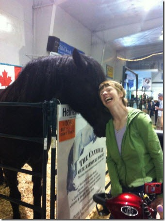 Glenda standing up to receive kisses and a nuzzle from a horse