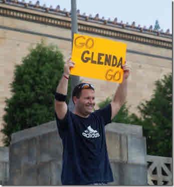"""An onlooker holding a sign """"Go Glenda Go"""""""