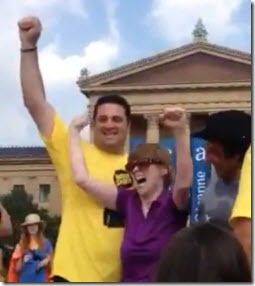 Felice Cantatore and Glenda Watson Hyatt raising arms in victory atop the Rocky steps, with Mike Kunda