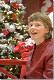 A smiling Glenda in front of a Christmas display