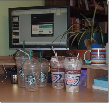 Several Starbucks and Tim Horton's coffee cups on my desk