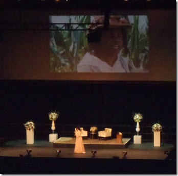 Oprah speaking on stage with a scene from the Color Purple on the screen behind her