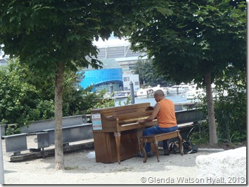Man playing a piano under the trees