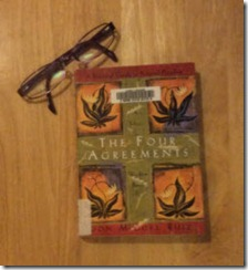 Reading glasses set beside Don Miguel Ruiz's The Four Agreements